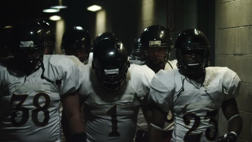 Football team walks down a dark tunnel towards the field before a game | Shutterstock HD Video #4706294