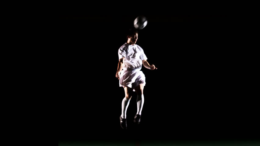 An isolated soccer player jumps up and heads the ball in the air on black - HD stock footage clip