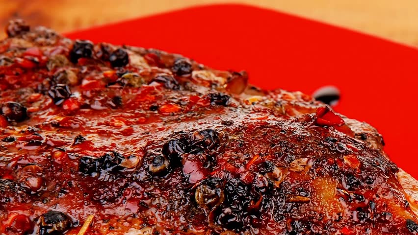 savory on red plate: grilled meat shoulder with tomato and chives on wooden table 1920x1080 intro motion slow hidef hd
