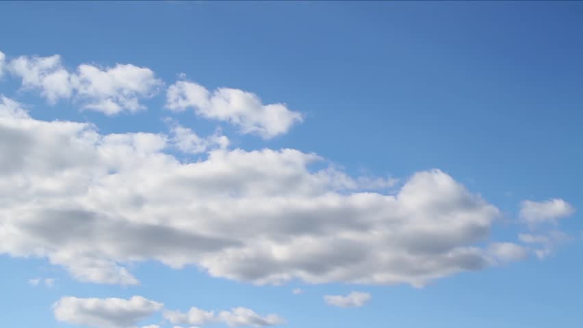 Beautiful white clouds soar across the screen in time lapse fashion over a deep blue background. 30 second loop. - HD stock footage clip