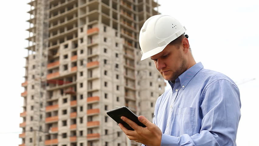 construction engineer with the tablet. pictures of the construction site