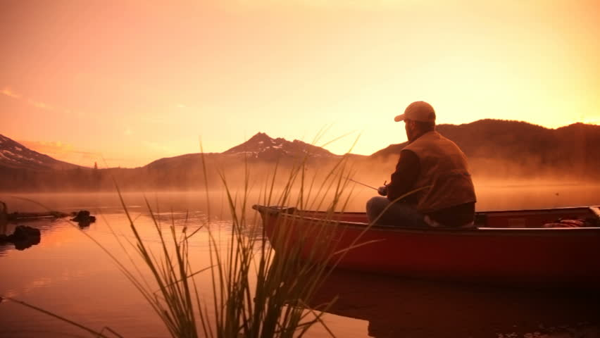 Man fishing in lake at sunrise