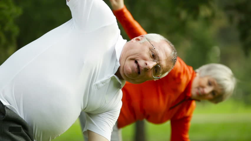 Healthy retirees doing a windmill arms exercise in an energetic pace - HD stock footage clip