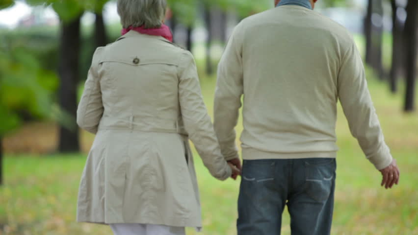 Senior couple taking an unhurried walk along the park lane