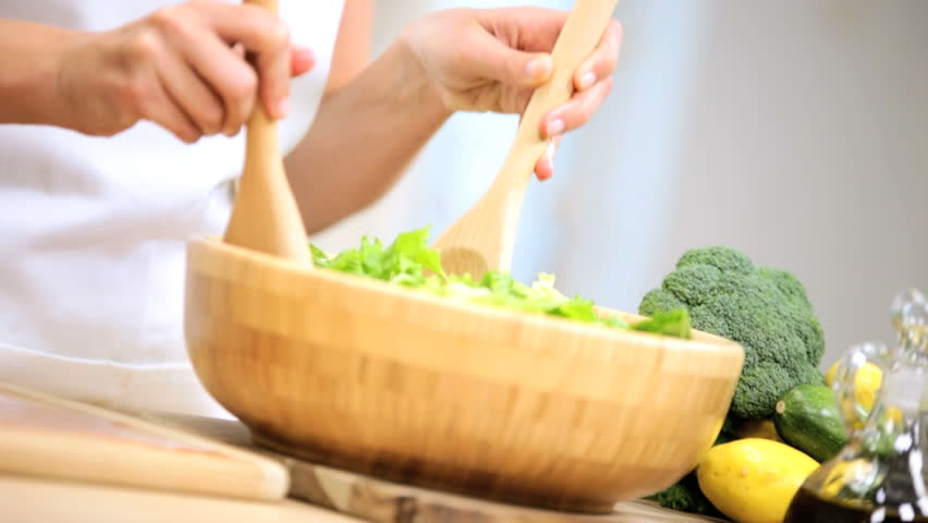 Health conscious young woman tossing a tasty organic green salad