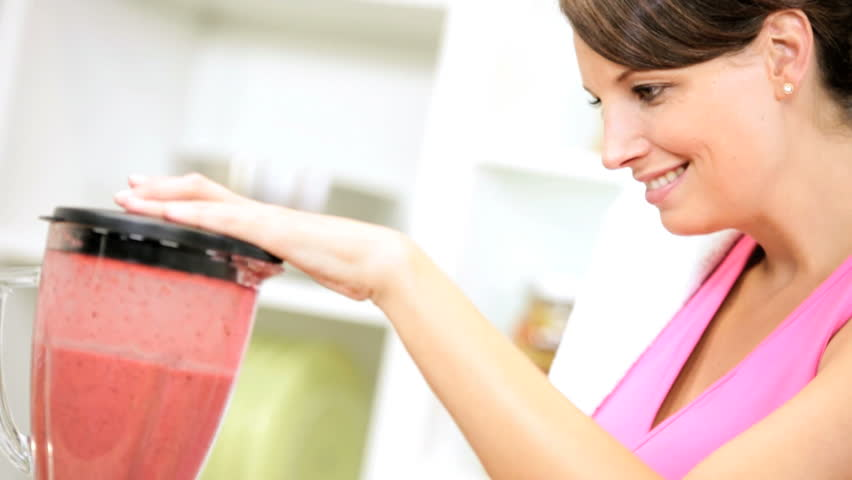 Young woman preparing a delicious homemade fruit smoothie after exercising at a health club