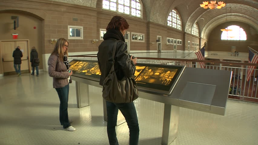 NEW YORK - CIRCA OCTOBER 2011 - Visitors look at explanation of hall in the Ellis Island Immigration Museum in October 2011. - HD stock video clip