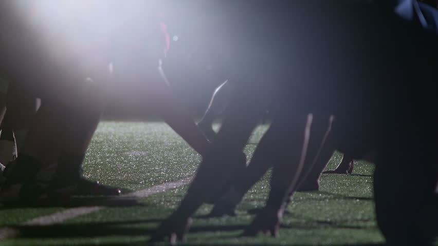 Close up view of football player's hands on the ground ready to snap the ball