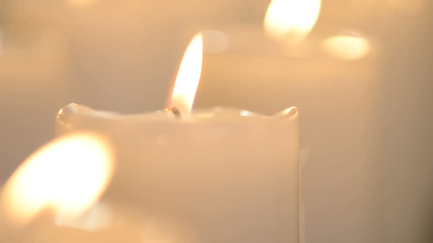 edited shot of a white candle and multiple white candles
