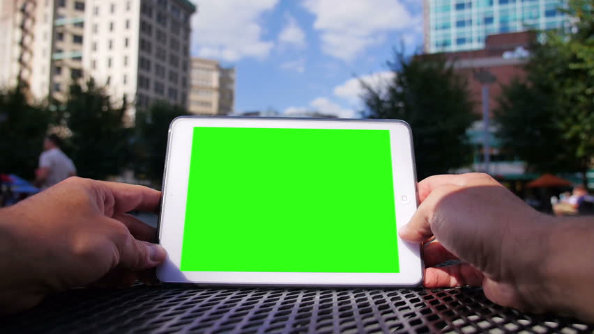 A man uses a tablet computer outside at Market Square in downtown Pittsburgh Pennsylvania.  Green screen and corner markers included for advanced motion tracking. | Shutterstock HD Video #4767638