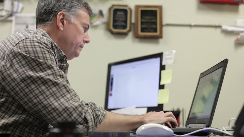 A handsome mature man in his office sitting at his desk working with two computer screens. - HD stock footage clip