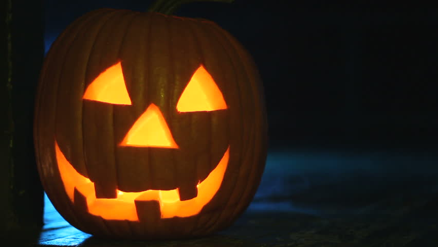 Glowing jack-o-lantern sitting on a porch with eerie smoke rising around it, ready for Halloween. | Shutterstock HD Video #4775882