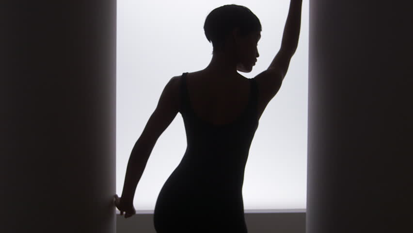 Rear view of black woman dancing in front of bright light - HD stock video clip