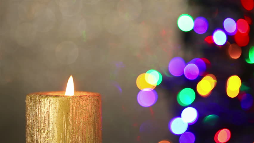 Flame Of Candle Burning With Christmas Tree Lights In The