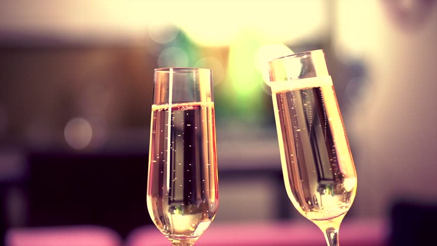 Champagne. Two Glases with Sparkling Champagne Toasting over Holiday Bokeh Blinking Background. Slow motion.