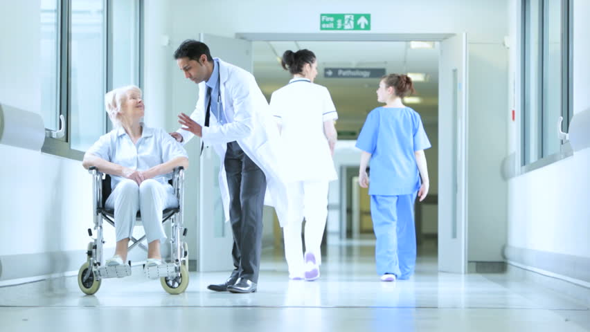 Hallway view in busy modern medical facility with medical professionals and doctor chatting with wheelchair-bound patient