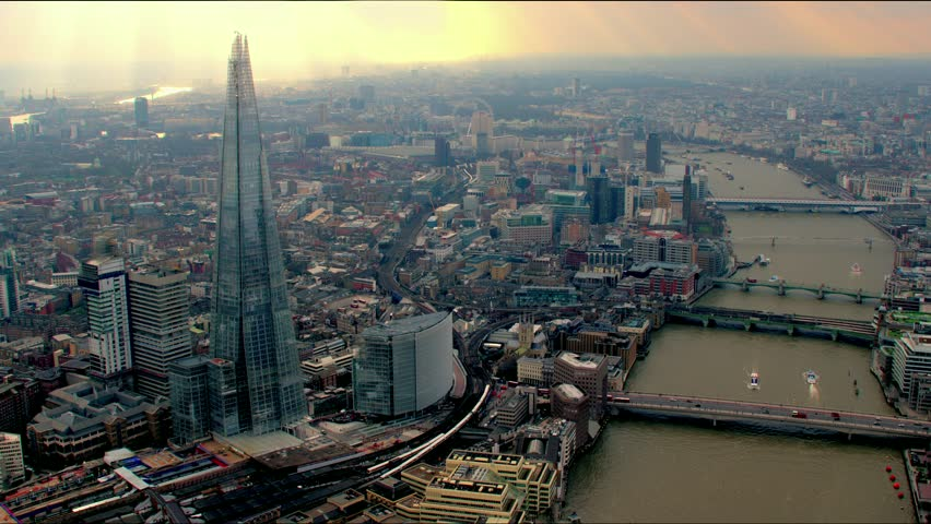 Panoramic aerial shot along the River Thames in Central London, UK. Features The Shard building, bridges and the Millennium Wheel / London Eye in the background.