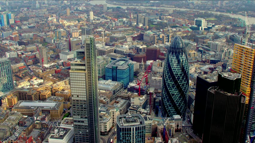 Dramatic aerial shot of the City of London financial district skyline. Features the Gherkin / 30 St Mary Axe building - shot then reveals Tower Bridge.   Shutterstock HD Video #4835516