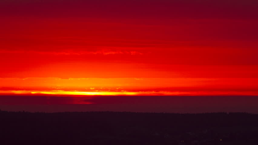 Fiery red sunrise under storm clouds during a rainstorm. Raindrops create a fake reflection effect.  - HD stock footage clip