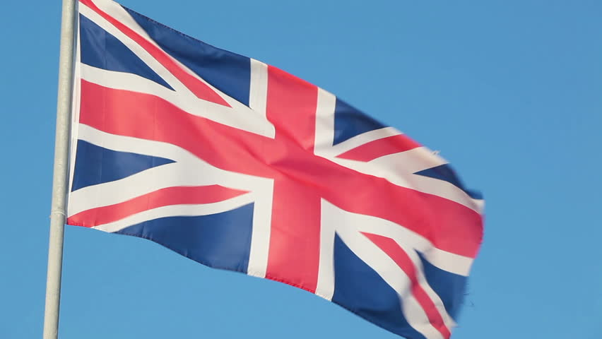 England national flag waving on flagpole on blue sky background