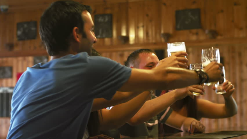 A group of friends drink beer at a bar