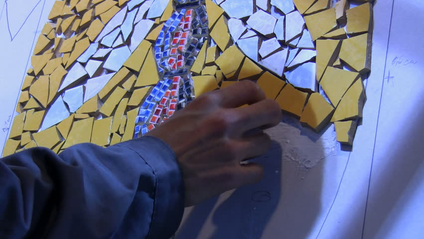 A hand of artist is sticking small colorful pieces of tiles onto vertical background creating mosaic picture | Shutterstock HD Video #4857035