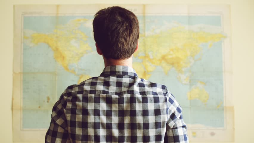Young tourist man looking at world map