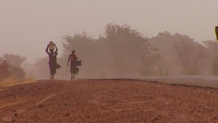 Women walk carrying goods on their heads through the Sahara desert in mali.