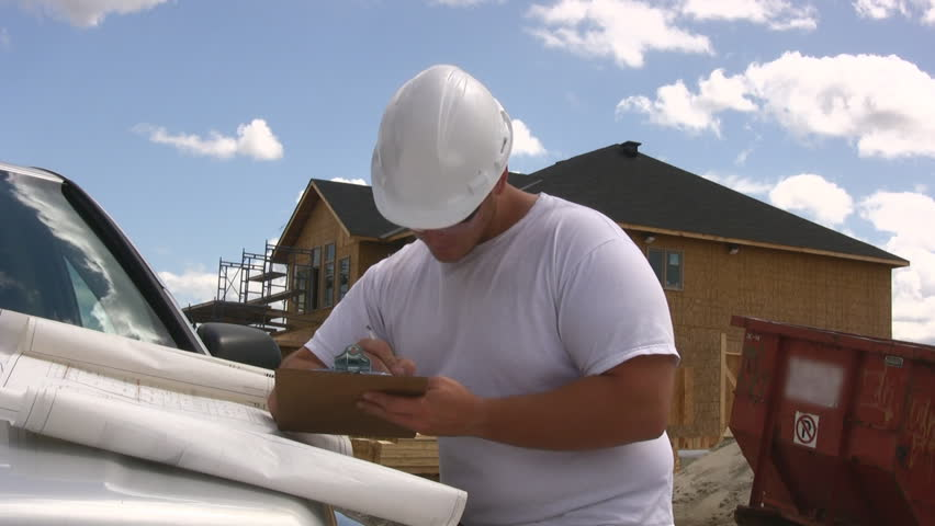 Builder Making Notes On A Clipboard