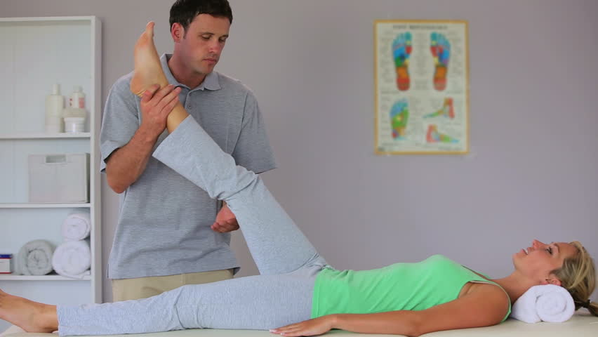 Physiotherapist moving his patients leg and talking in his office