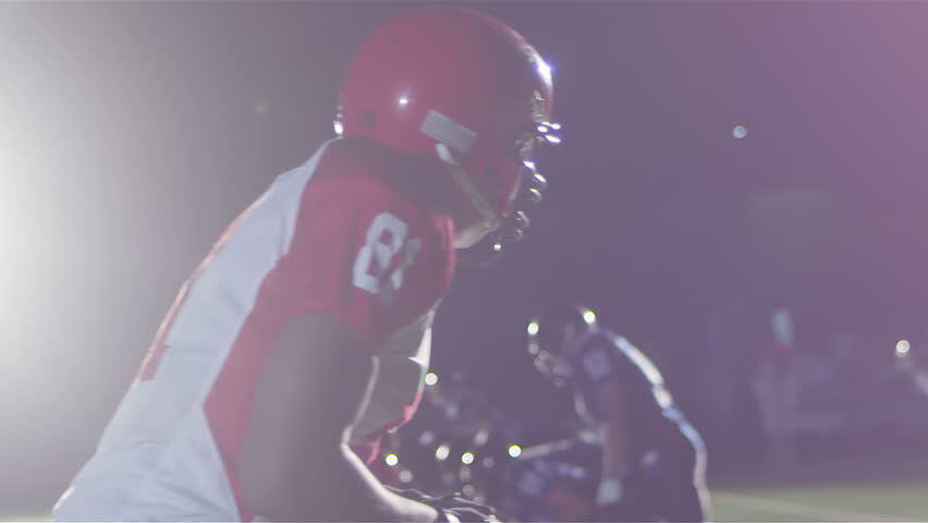 Close up tracking shot of a football player catching a pass while being defended