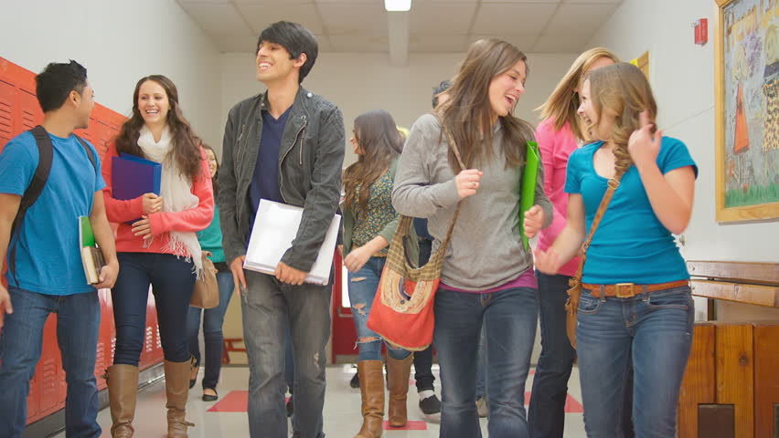 A group of students walk up the stairs and down the hallway towards the camera in slow motion