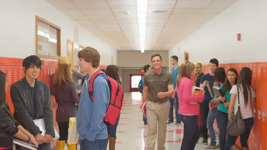 A School Hallway Is Full Of Students Standing In Groups ...