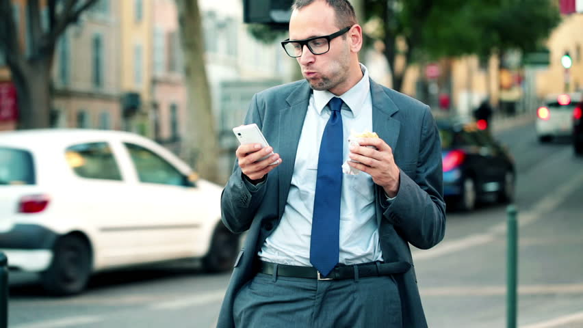 Businessman with smartphone eating sandwich by city street