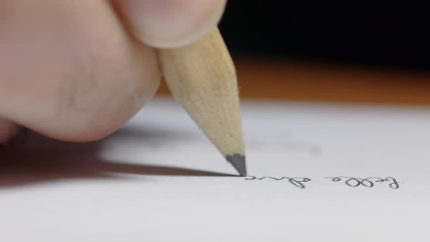 A hand with a wooden pencil writes on a paper. Concept for school projects.