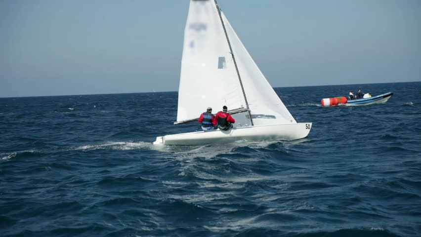 Two man sailing on sea with assistance boat in background - HD stock footage clip