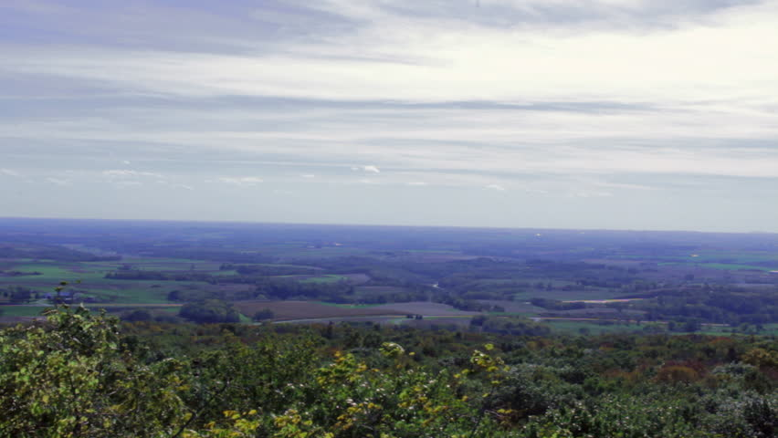 An expansive view of Wisconsin countryside in the Fall. Shot from the Blue Mounds State Park hill, clouds soar over treetops bright with fall colors, green fields, farmhouses and rural homesteads. - HD stock footage clip