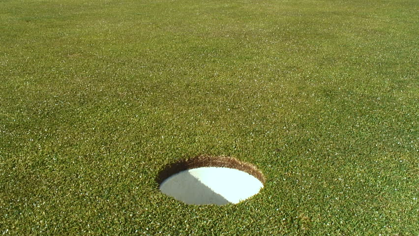 A close up of a golf ball rolling into a hole.  - HD stock video clip