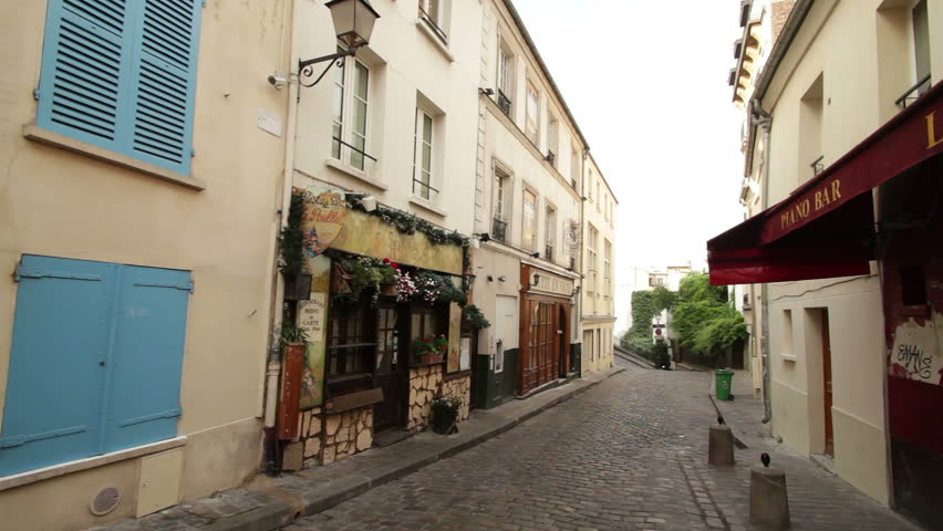 PARIS, FRANCE - CIRCA JULY 2013: Young man on a moped drives down a street at the famous Montmartre district in Paris. | Shutterstock HD Video #4932815