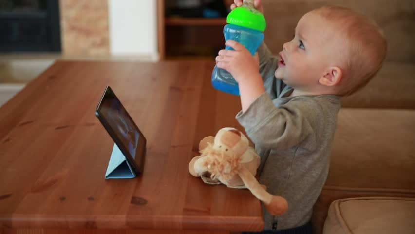 A cute little baby boy watching a movie on a tablet in the living room of his house - HD stock video clip