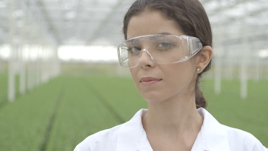 CU Scientist wearing safety glasses in a greenhouse - HD stock video clip