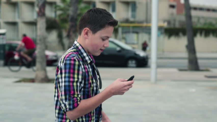Boy using smartphone and walking in the city