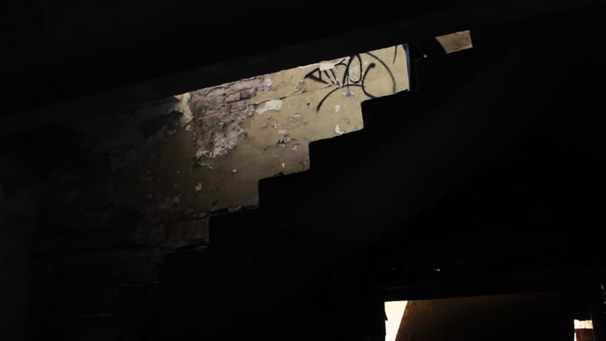 Horror scene, masked killer with machete chasing a girl in abandoned building through the hallways.The girl running down the stairs, murderer with hood go for her.