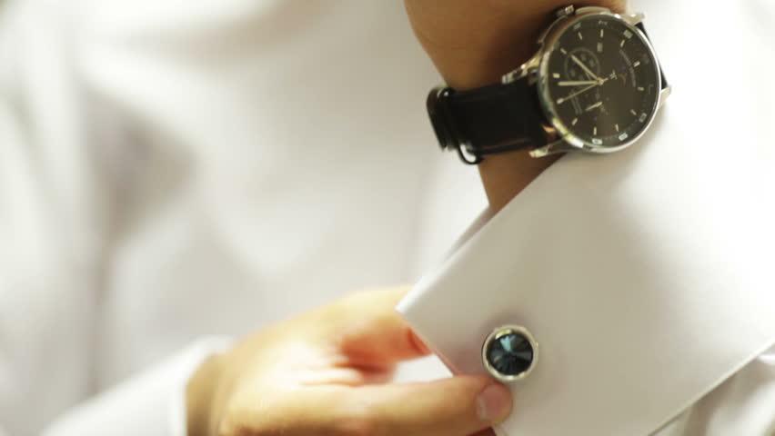 Man wears shiny cufflinks and watching the clock