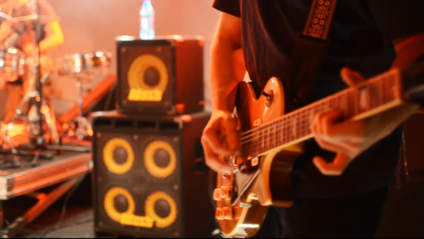 man playing electric guitar on stage at a rock concert
