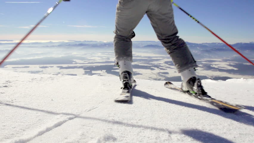 Slow Motion Rear View Of Skier Skiing Down The Snowy Slope With Spectacular Mountain Peaks Panoramic View