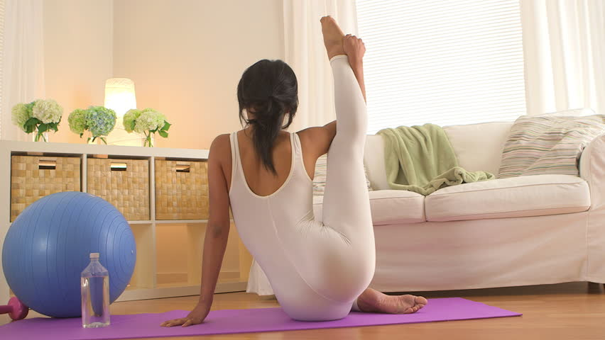 Woman sitting on yoga mat in living room stretching legs for Living room yoga sessions