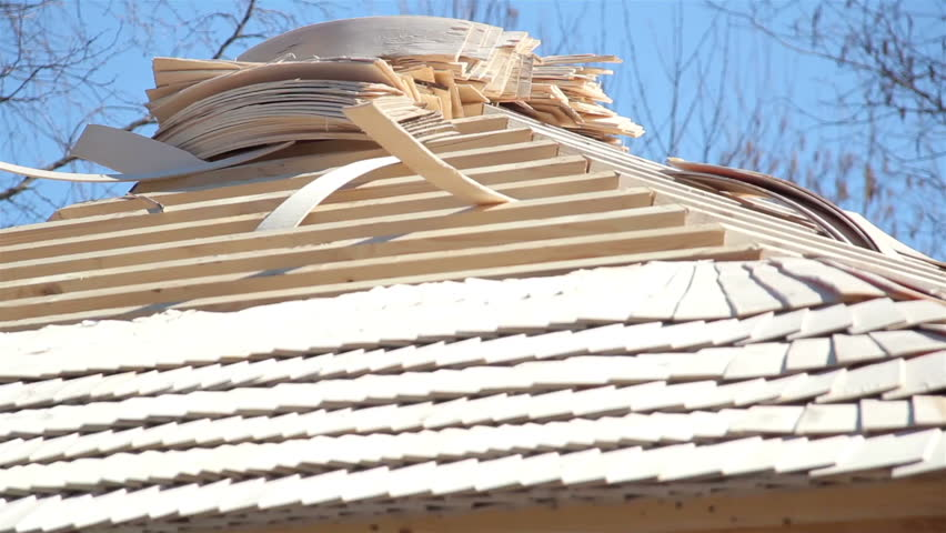 Roof tiles piled on top of the roof and is ready to be placed by the roofers working on the roof. Cedar wooden shingle on the roof carpentry roofing roofworking build economy industry.