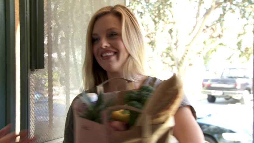 Attractive brunette woman orders groceries on a tablet computer and has them delivered by a young blonde woman.  She signs for the delivery on a smartphone.  Sequence intended for commercials.