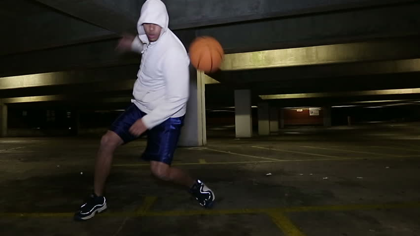 Hooded street ball basketball player dribbling the basketball with skill - HD stock footage clip